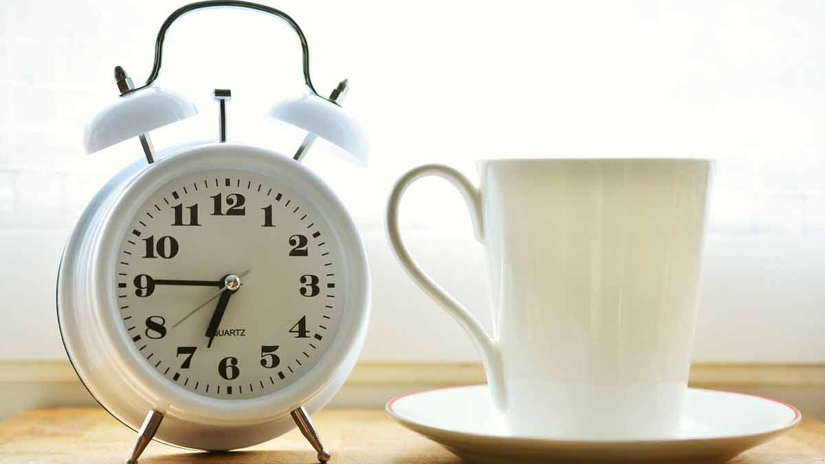 White cup and alarm clock